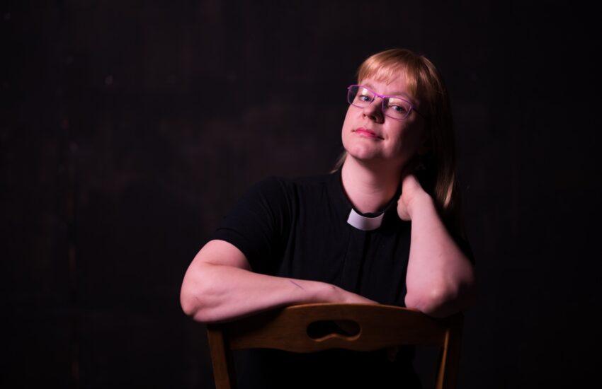 Nainen papin paidassa istuu ja nojaa toisella kädellä tuoliin, toisella kaulaan.