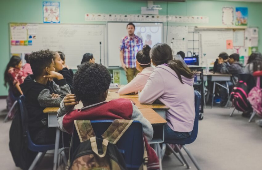 Opettaja seisoo opiskelijoiden edessä luokassa