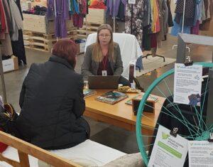 Kaksi naista keskustelee pöydän ääressä