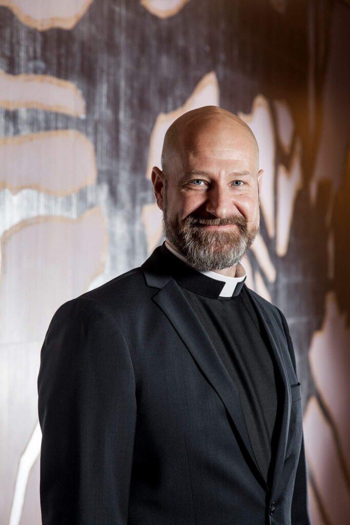 Heikki Arikka, piispanvaaliehdokas, mies papin asussa värikkään seinän edessä. Valkoihoinen, kalju, parta, katsoo kameraan hieman hymyillen.