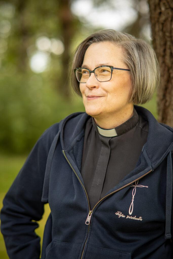 Kaisa Huhtala, valkoihoinen nainen papin paidassa ja tummansinisessä hupparissa katsoo hymyillen etuoikealle. Hänellä on silmälasit ja harmaasävyiset korvan alapuolelle ulottuvat hiukset.