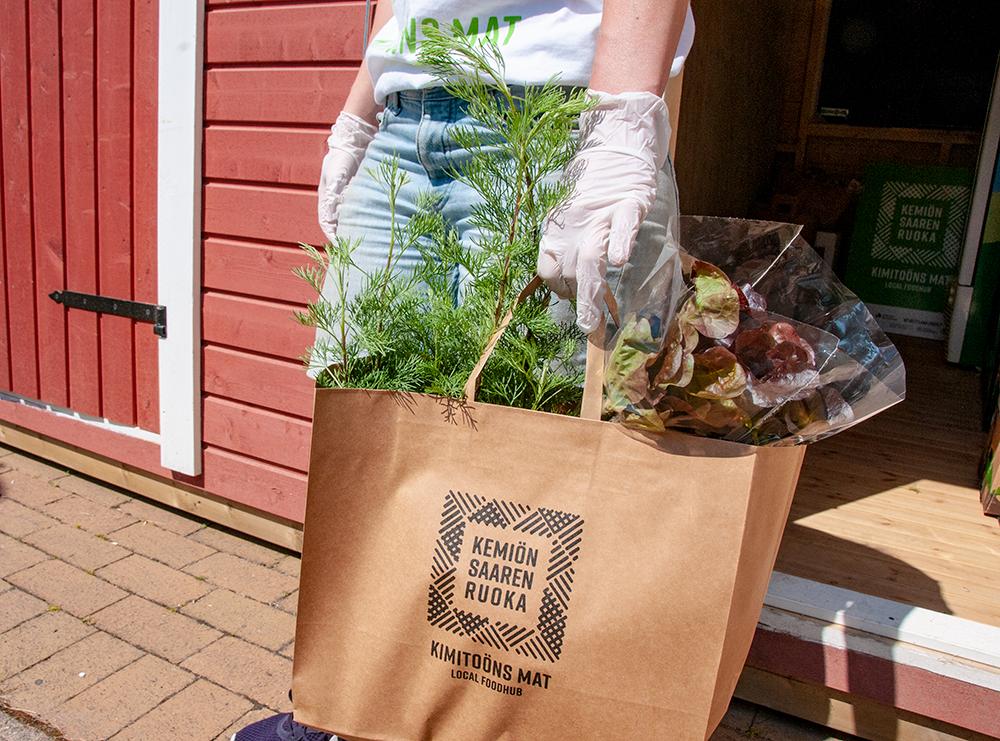 Stella Törnroth pitelee kädessään Kemiönsaaren foodhub-paperikassia, josta pilkistää tuoretta salaattia ja yrttejä.