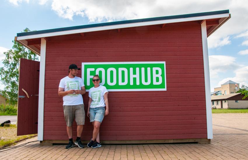 Punainen foodhub-jakelupistekioski. Kioskin edessä seisovat hymyillen Stella Törnroth ja Jonas Bergström.