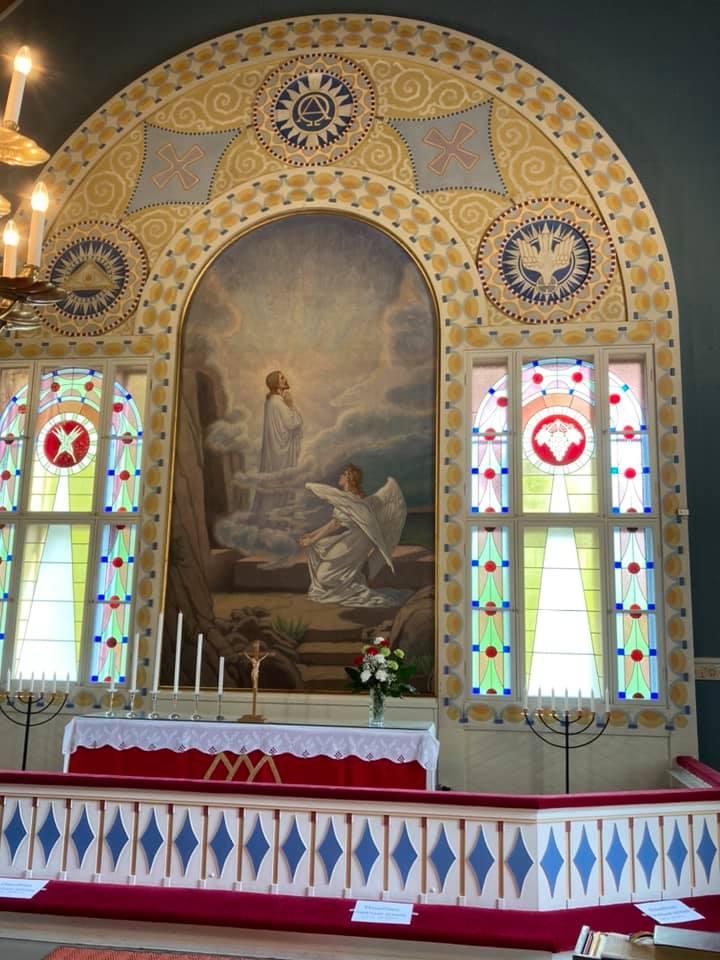 Kirkon alttari ja alttaritaulu, jossa aiheena Jeeuksen ylösnousemus.